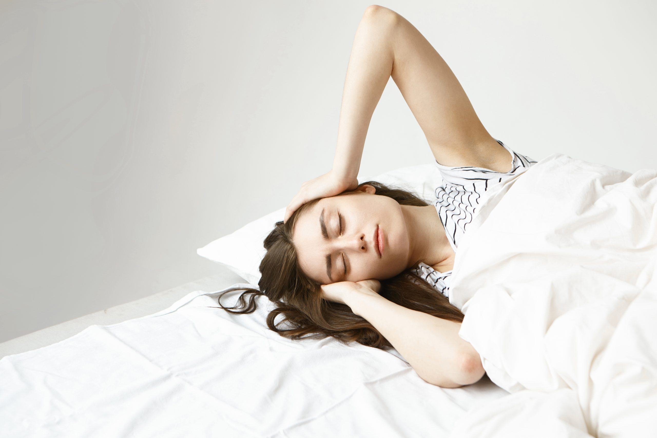 people insomnia sleeping disorders concept indoor shot beautiful sad young dark haired woman lying white bedclothes her room massaging head trying get asleep after long working day scaled