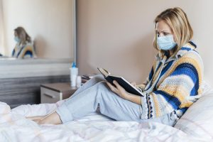 woman with book medical mask quarantine