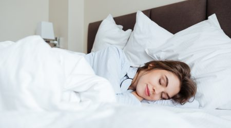 Photo of cheerful young lady dressed in pajama lies in bed at home under a blanket sleeping.